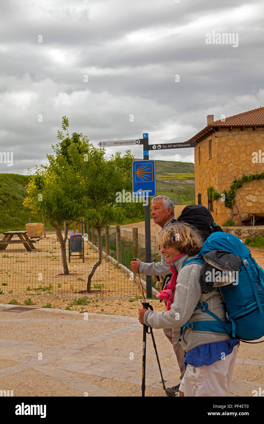 Pilgrims man and woman approaching the Spanish town of Castrojeriz while walking on the Camino de Santiago the way of St James - Stock Image