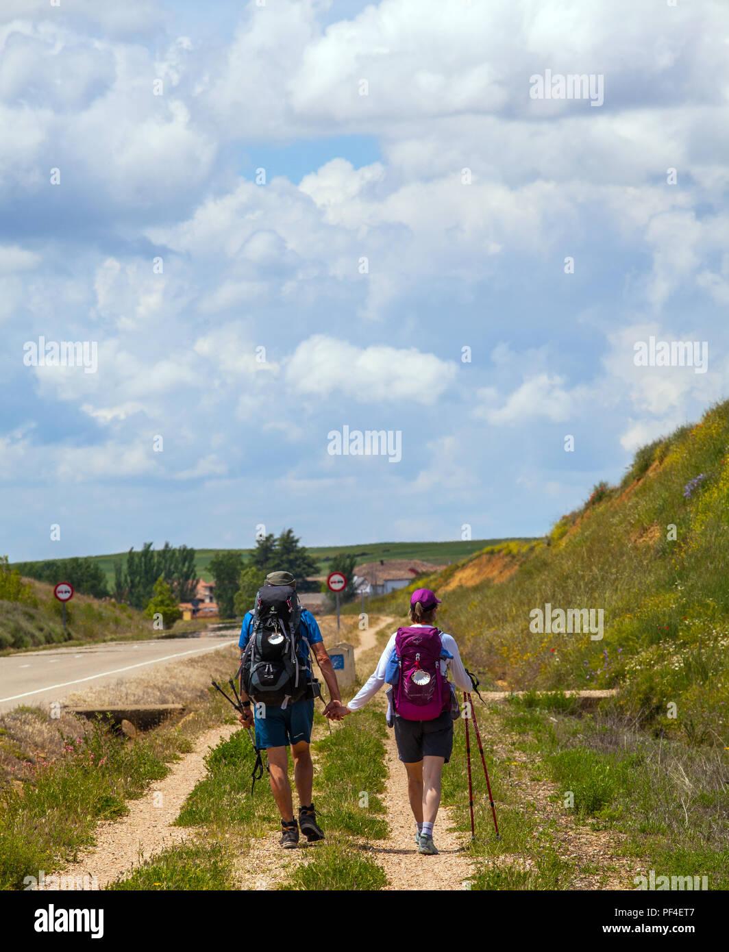 Man and woman couple pilgrims holding hands walking the Camino de Santiago the way of St James walking towards Villalcazar de Sirga Spain - Stock Image