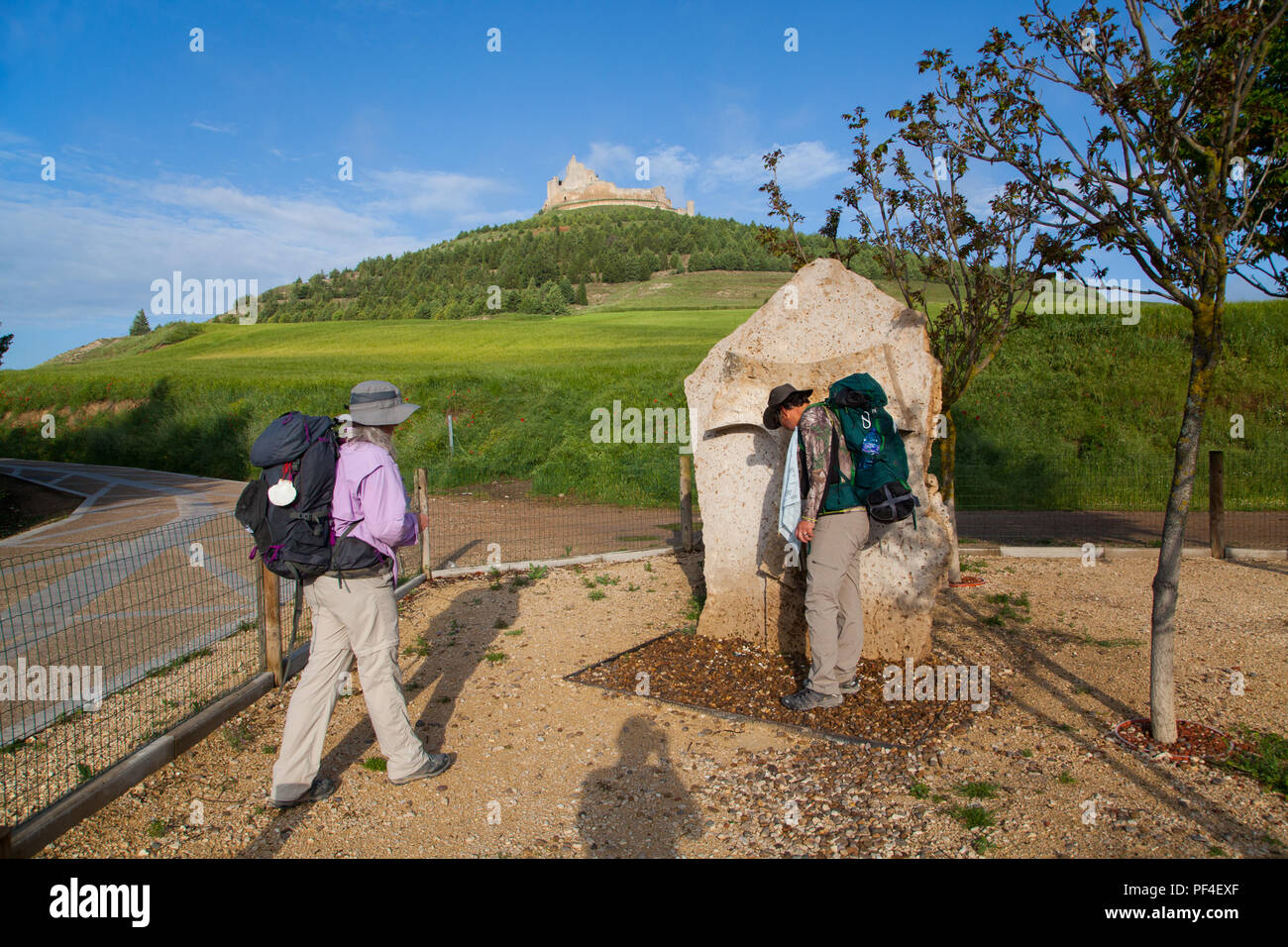 Pilgrims man and woman stopped to fill water bottles at a fountain in Castrojeriz while walking the Camino de Santiaga the way of St James Spain - Stock Image