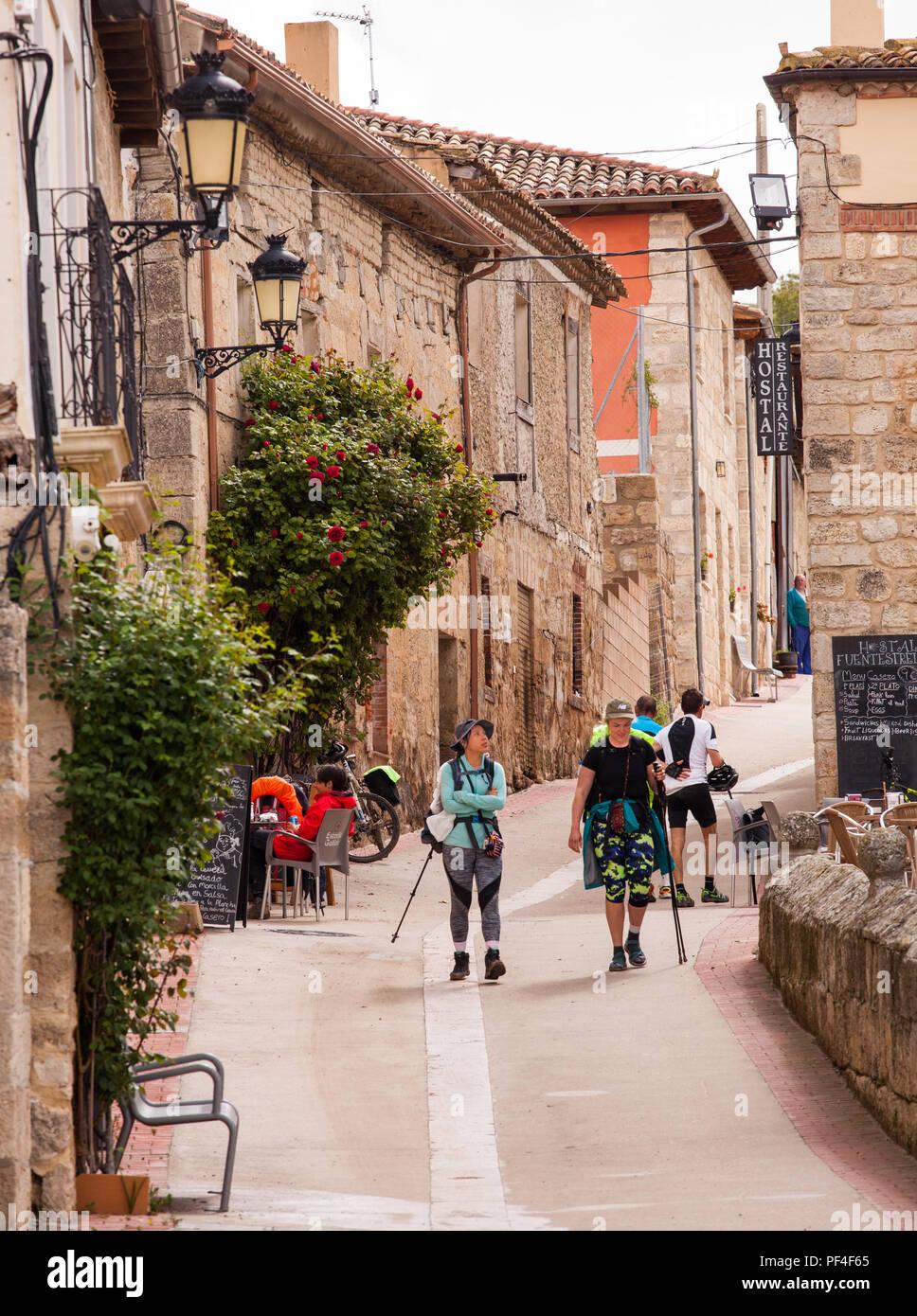 Pilgrims men and women walking on the way of St James the Camino de Santiago in the village of Hontanas Burgo Castille y Leon Spain - Stock Image