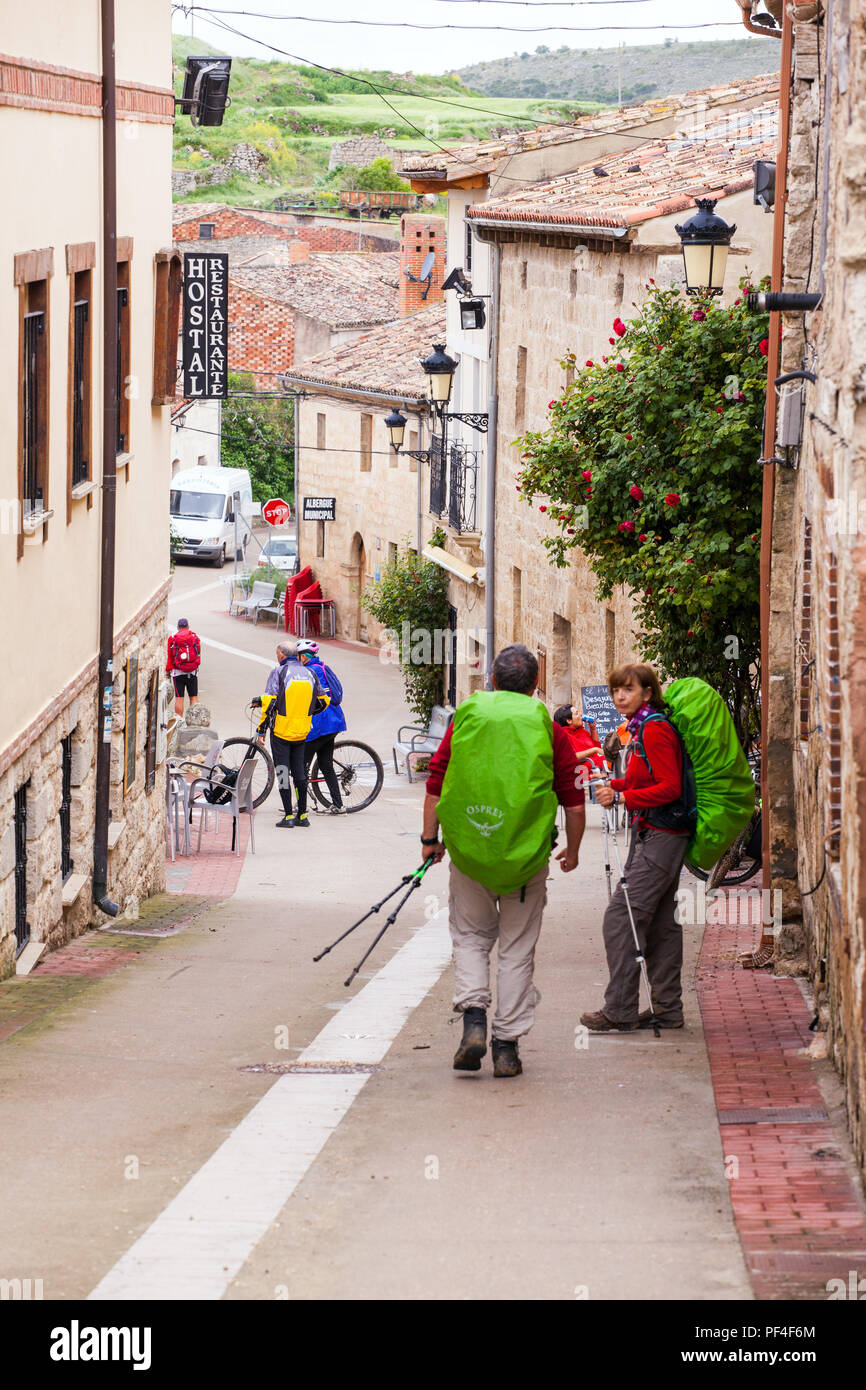 Pilgrims approaching the village of Hontanas while  walking on the way of St James the Camino de Santiago Burgos Castille y Leon Spain - Stock Image