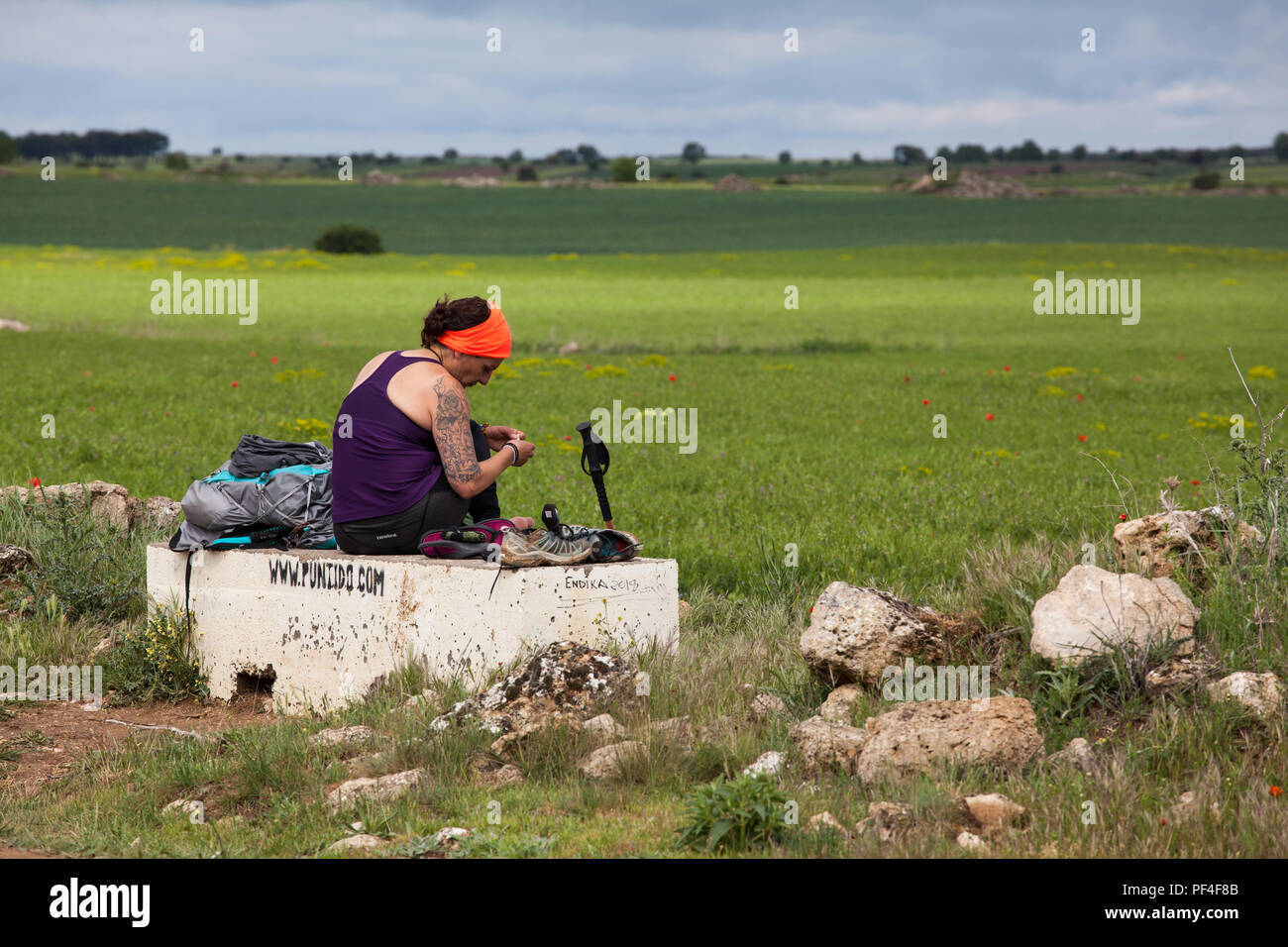 Woman pilgrim taking a rest while walking alone on the Camino de Santiago the way of St James near the village of Hontanas Burgos Spain - Stock Image