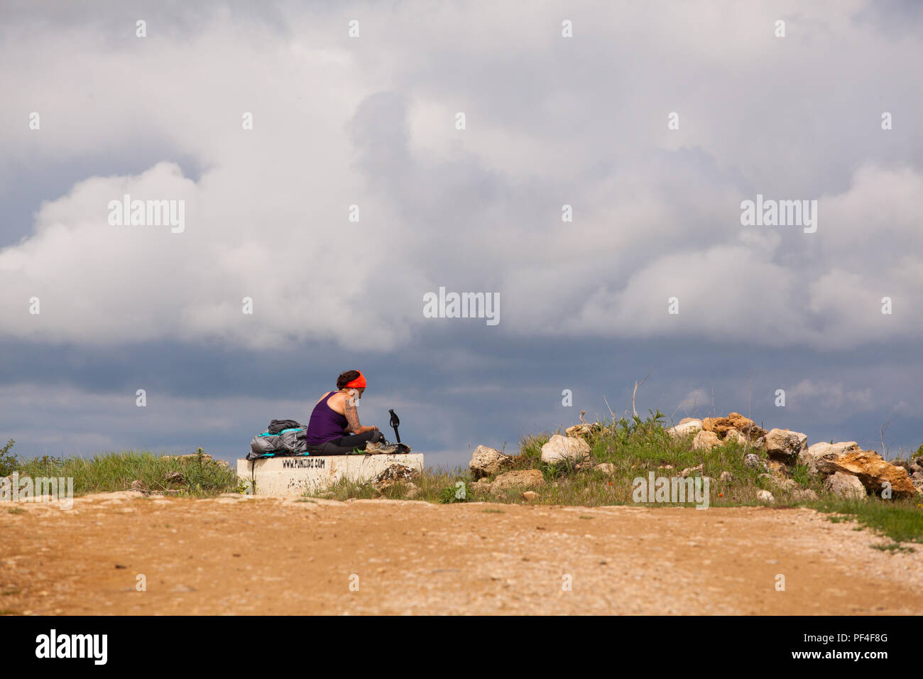 Woman pilgrim taking a rest while walking alone on the Camino de Santiago the way of St James near the village of Hontanas Burgos Spain Stock Photo