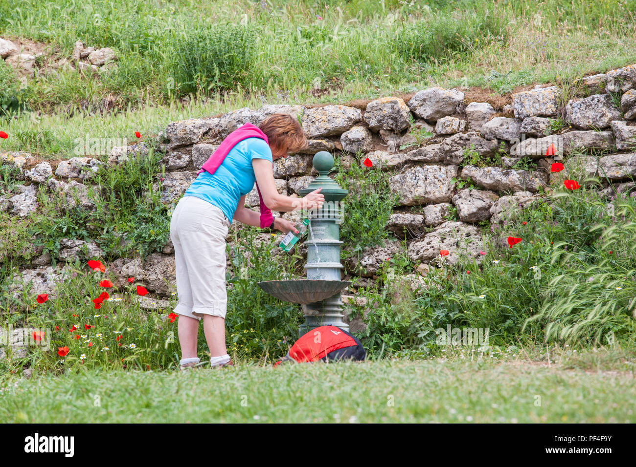 Woman pilgrim filling water bottle from a fountain in the village of Hontanas while walking the way of St James the Camino de Santiago Burgos Stock Photo