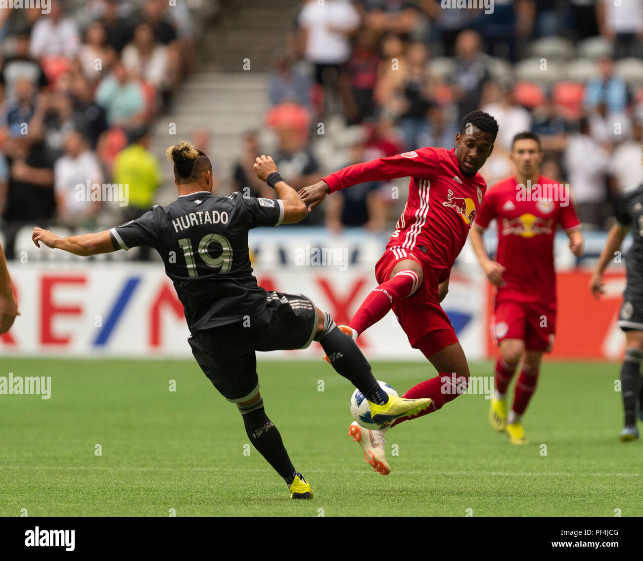 Vancouver, Canada. 18 August, 2018.  Michael Murillo (62) of New York Red Bulls, and Erik Hurtado (19) of Vancouver Whitecaps, battle for the ball. Vancouver Whitecaps vs New York Red Bulls, BC Place Stadium. © Gerry Rousseau/Alamy Live News - Stock Image