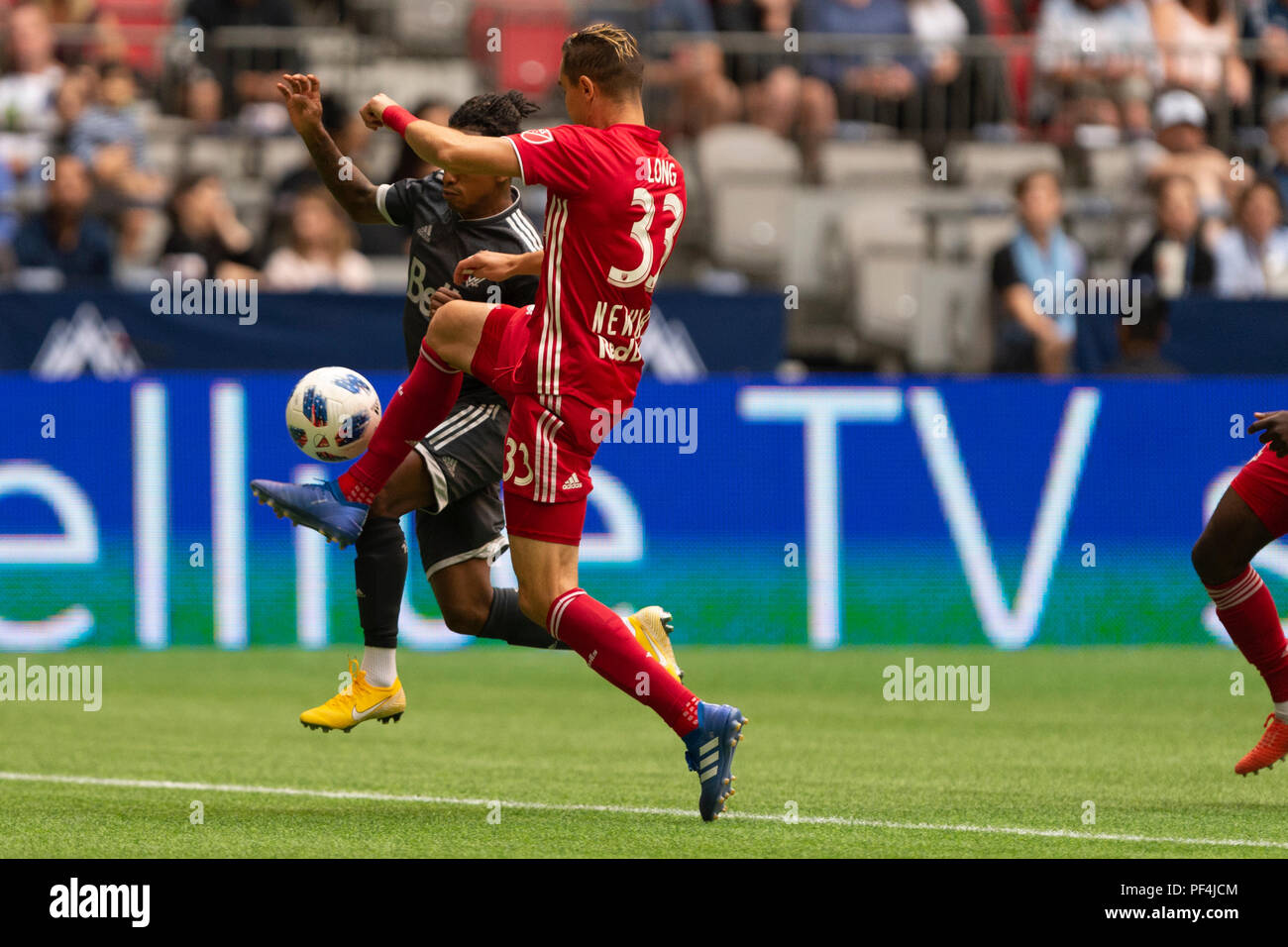 Vancouver, Canada. 18 August, 2018. Aaron Long (33) of New York Red Bulls and Yordi Reyna (29) of Vancouver Whitecaps, battle for the ball. Vancouver Whitecaps vs New York Red Bulls, BC Place Stadium. © Gerry Rousseau/Alamy Live News - Stock Image