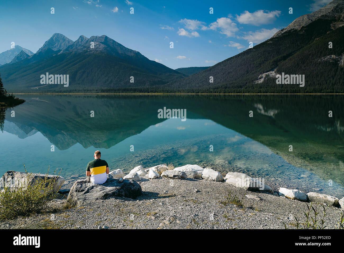 Man Reading in Quiet Contemplation, Spray Lake, Alberta, Canada - Stock Image