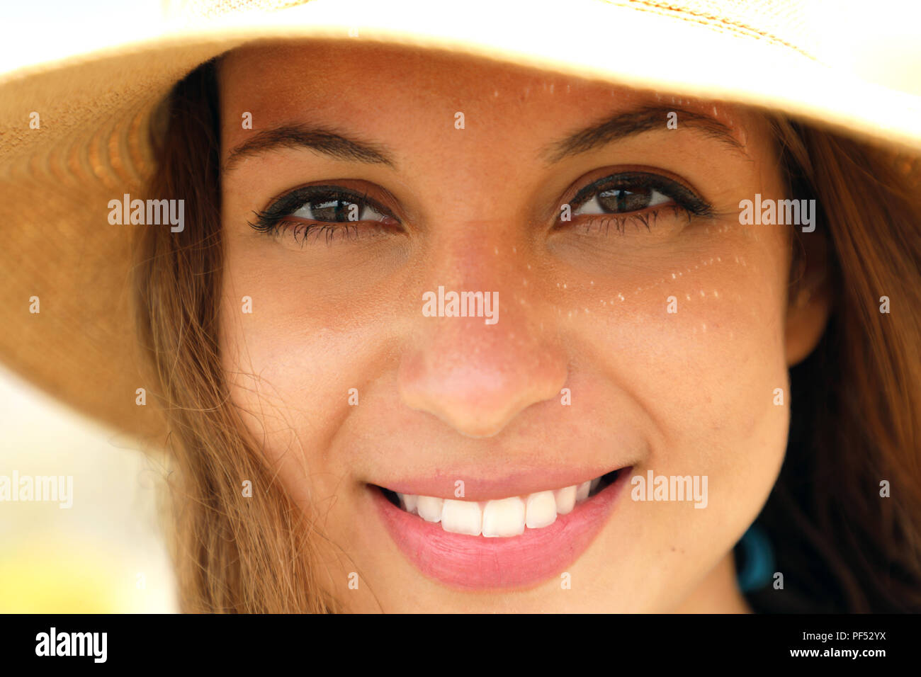 Extreme close up of young model face with straw hat smiling at camera under summer rays sun on the beach. Very close up of photogenic model for tannin - Stock Image