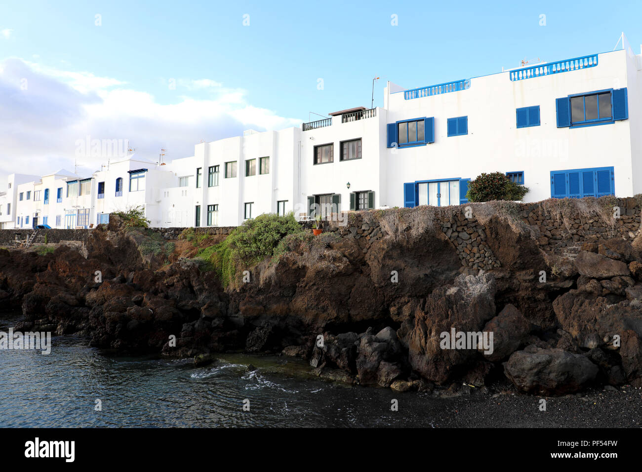 Typical canarian white houses in Punta Mujeres on sea rocks, Lanzarote Island Stock Photo