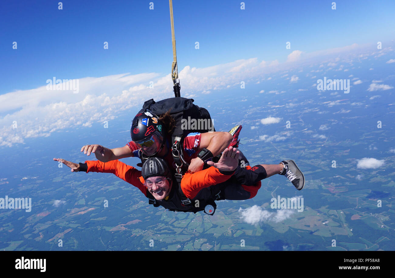 """U.S. Air Force Chaplain (Capt.) James Finley, 20th Fighter Wing chaplain, smiles at the camera as he falls from 15,000 feet Chester, S.C., Aug. 11, 2018. Finley put on a skydiving event, which he called the """"leap of faith"""" to help Airmen get out of their comfort zone. (Curtesy photo) Stock Photo"""