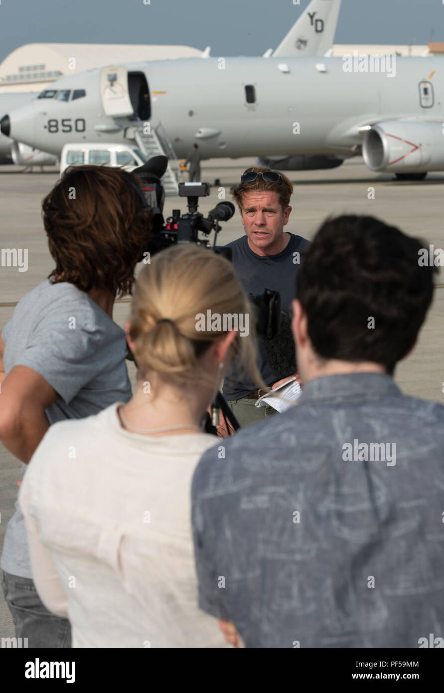 CNN Reporter Ivan Watson airs a live report after a flight on a U.S. Navy P-8A Poseidon Aug. 10, 2018, at Kadena Air Base, Japan. News agencies were invited to fly on the P-8A to learn about the Poseidon's abilities and the role it plays in the Pacific region. (U.S. Air Force photo by Staff Sgt. Micaiah Anthony) - Stock Image