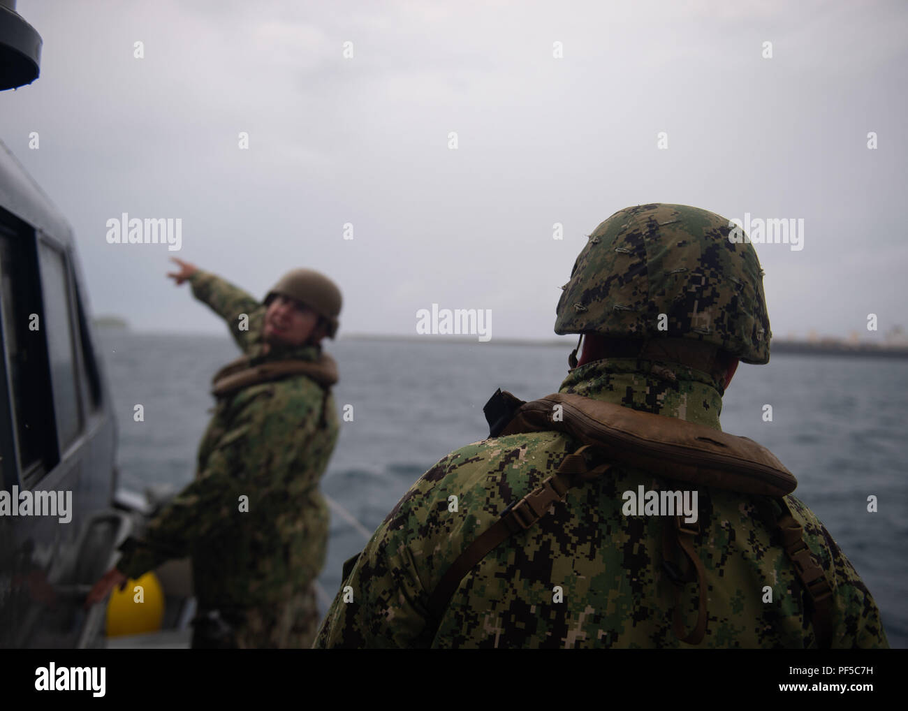 Hull Technician 2nd Class Tim Salyer, left, and Gunner's Mate Seaman Noah Vacha, right, assigned to Coastal Riverine Squadron (CRS) 3, stand watch as lookouts on a Mark VI patrol boat assigned to Coastal Riverine Group (CRG) 1 Det. Guam, in Apra Harbor Aug. 16, 2018. CRG 1 Det. Guam conducts maritime security operations across the full spectrum of naval, joint and combined operations providing additional capabilities of port security, embarked security, and theater security cooperation.  CRG 1 Det. Guam is assigned to Commander, Task Force (CTF) 75, the primary expeditionary task force respons - Stock Image