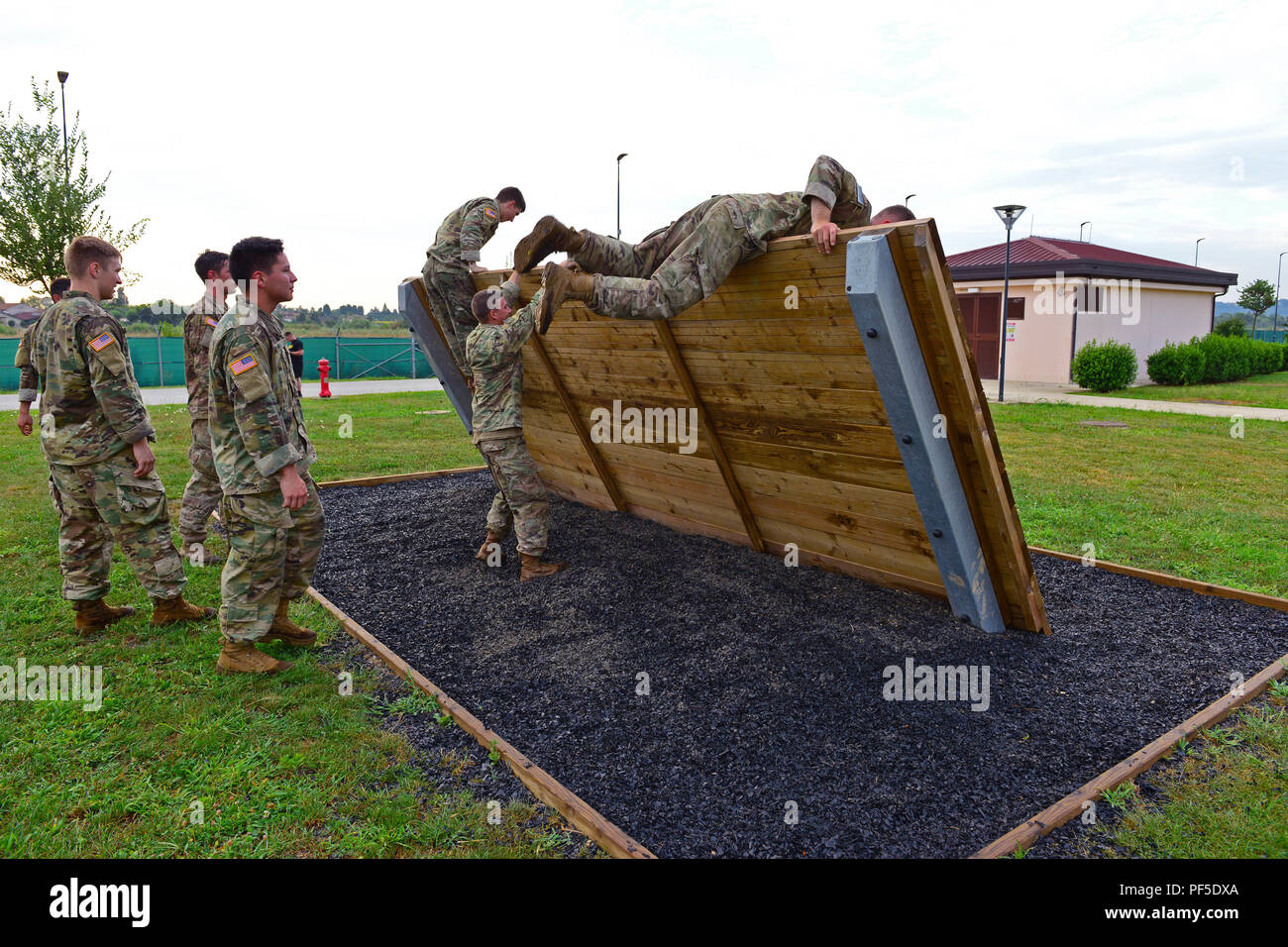 U.S. Army Paratroopers, assigned to the 2nd Battalion, 503rd Infantry Regiment, 173rd Airborne Brigade, jump over a slanted wall during the obstacle course at Caserma Del Din, Vicenza Italy Aug. 10, 2018. The obstacle course challenges Soldiers in their endurance, form and ability to physically navigate difficult tasks. The course also demands Soldiers to push themselves to conquer fears and gain confidence in their accomplishments. The 173rd Airborne Brigade is the U.S. Army Contingency Response Force in Europe, capable of projecting ready forces anywhere in the U.S. European, Africa or Centr - Stock Image