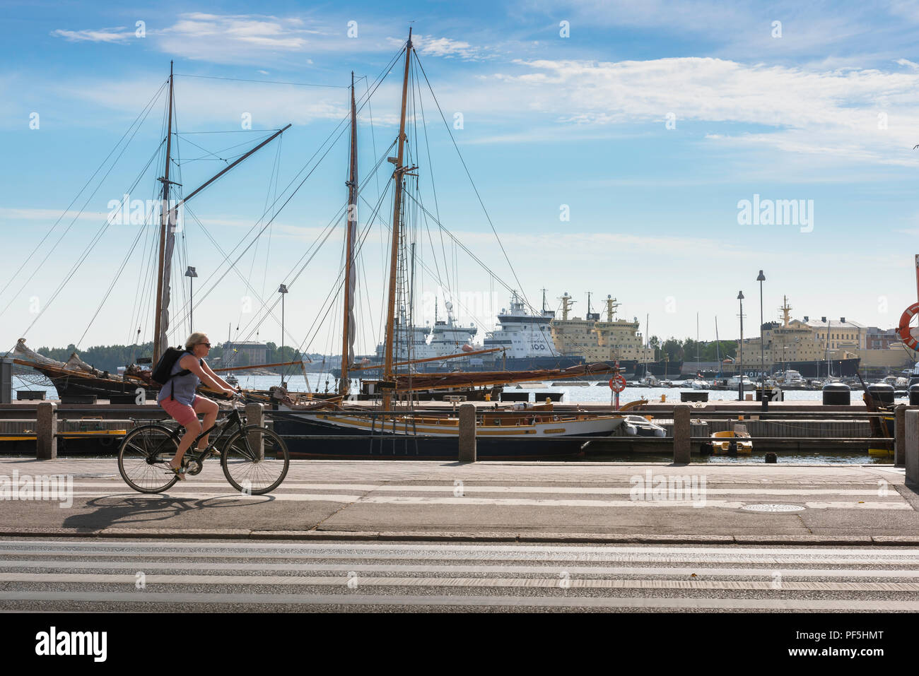Finland cycling summer, view of a woman cycling along the harbor front in the city of Helsinki on a summer morning, Finland. Stock Photo