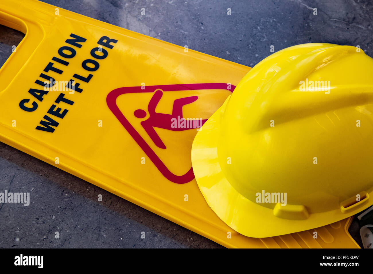 yellow plastic sign showing caution warning of wet floor with yellow protective helmet lying on floor - Stock Image