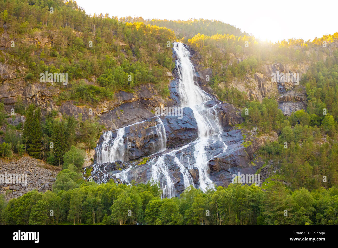 Beautiful waterfall in mountains at sunset lights, Norway - Stock Image