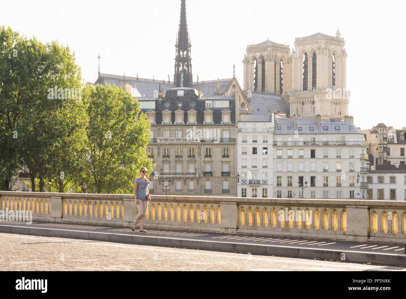 Paris cityscape - Woman walks along the Louis Philippe bridge on a late afternoon in Paris. France. - Stock Image