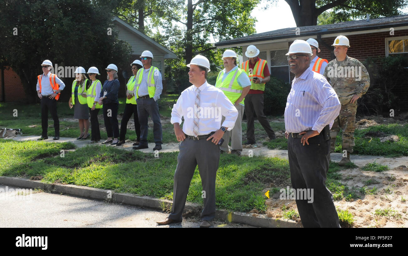 Garrison staff members, contractors and housing officials watch as Col. Hollie J. Martin, garrison commander, takes a ceremonial turn at demolishing a housing unit using an excavator in the Jefferson Terrace neighborhood Aug. 15. Thirty-four housing units will be demolished to make room for 34 new quarters designated for officers. The construction is scheduled to be completed by September of 2019. - Stock Image