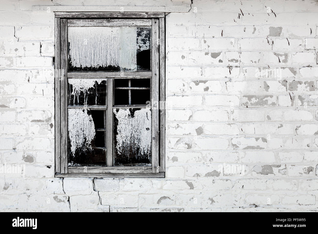 Old aged cracked white brick wall with broken window. Shattered dirty window glass and iron grates with black background. Abandoned building concept - Stock Image