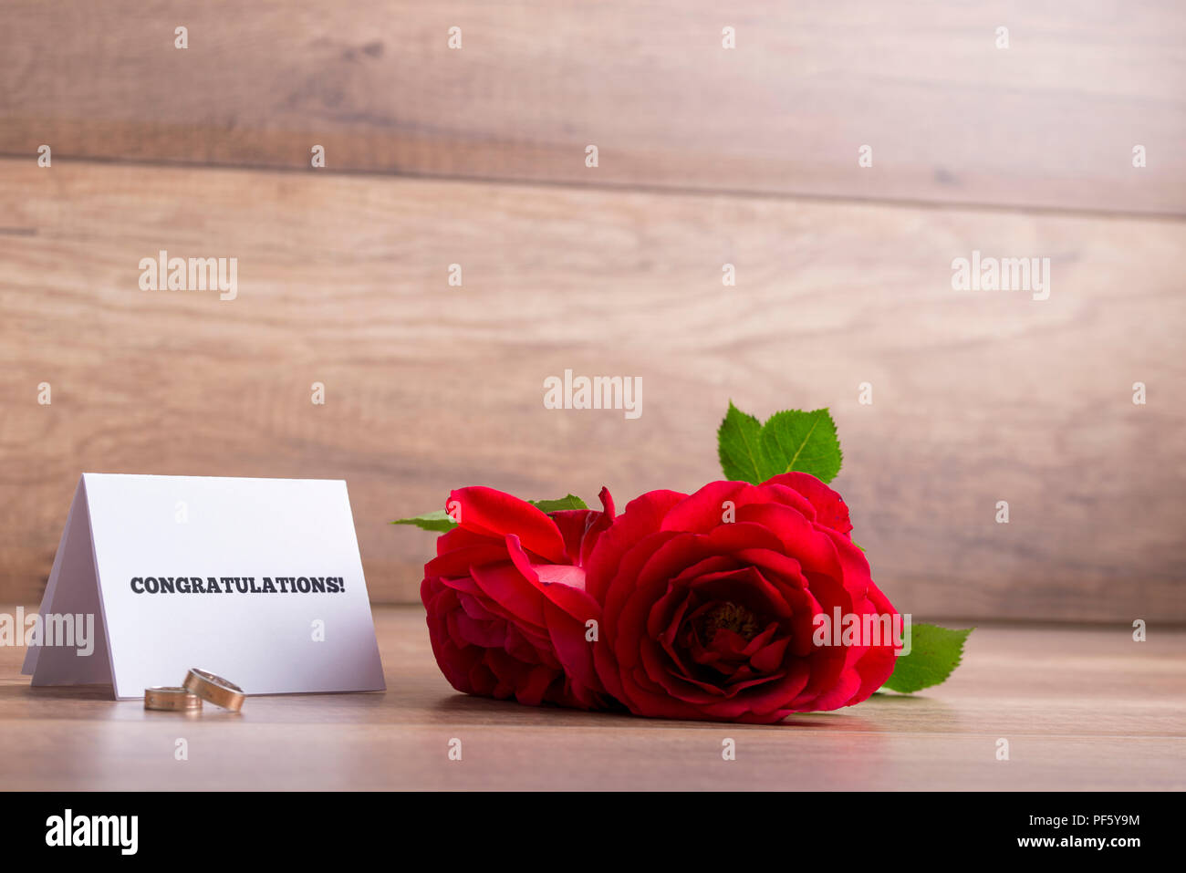 Wedding greetings stock photos wedding greetings stock images alamy wedding greetings white card with congratulations sign wedding rings and two red roses on m4hsunfo