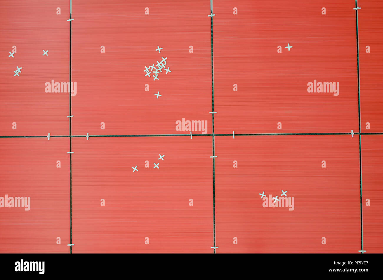Top view of unfinished red ceramic tiles with tile spacers. - Stock Image