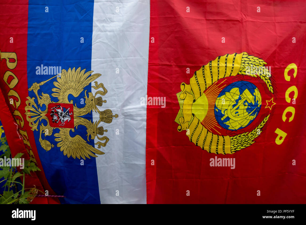 Flags of the Russian Federation and the USSR hang on a street in Russian town - Stock Image