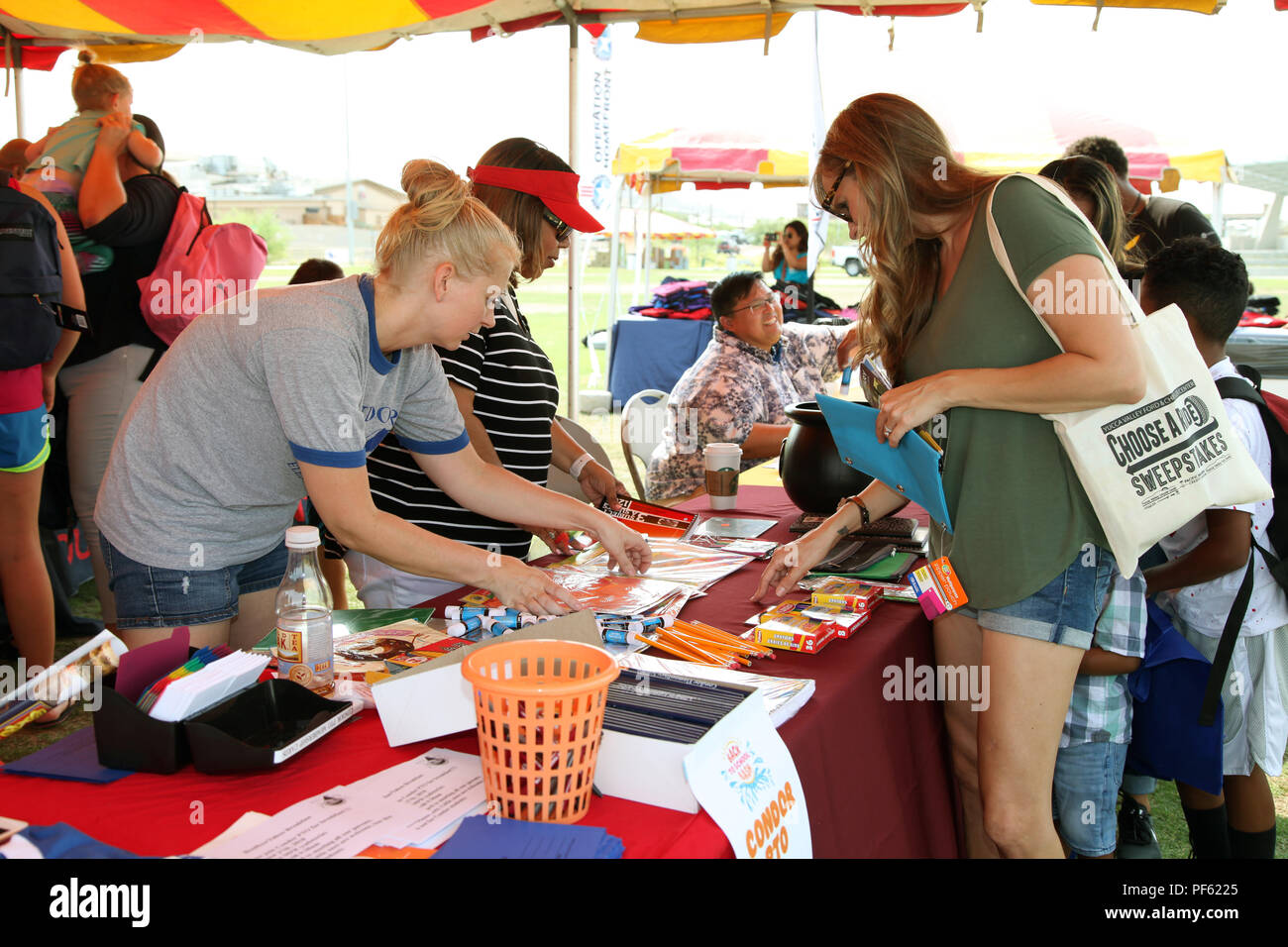 Family members peruse offerings during the Back to School Bash at Victory Field, Marine Corps Air Ground Combat Center, Twentynine Palms, Calif., Aug. 10, 2018. About 1,500 attended the event hosted by Marine Corps Community Services and the Combat Center School Liaison. (Marine Corps photo by Kelly O'Sullivan) - Stock Image