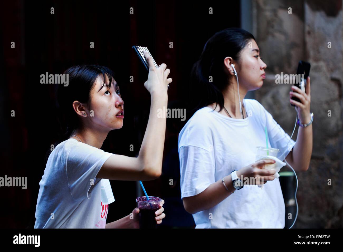 Two Asian women using their smartphones, Gracia, Barcelona, Spain. - Stock Image