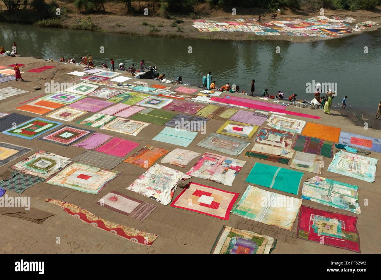 People washing and drying bed sheets, durries at Krishna River, Wai, Satara, Maharasthra, India - Stock Image