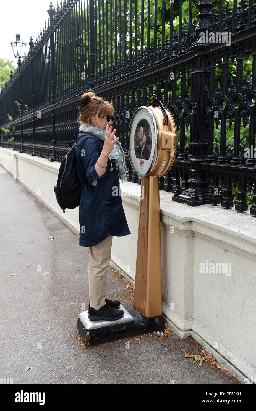 Woman weighing herself on public scales in Vienna, Austria - Stock Image
