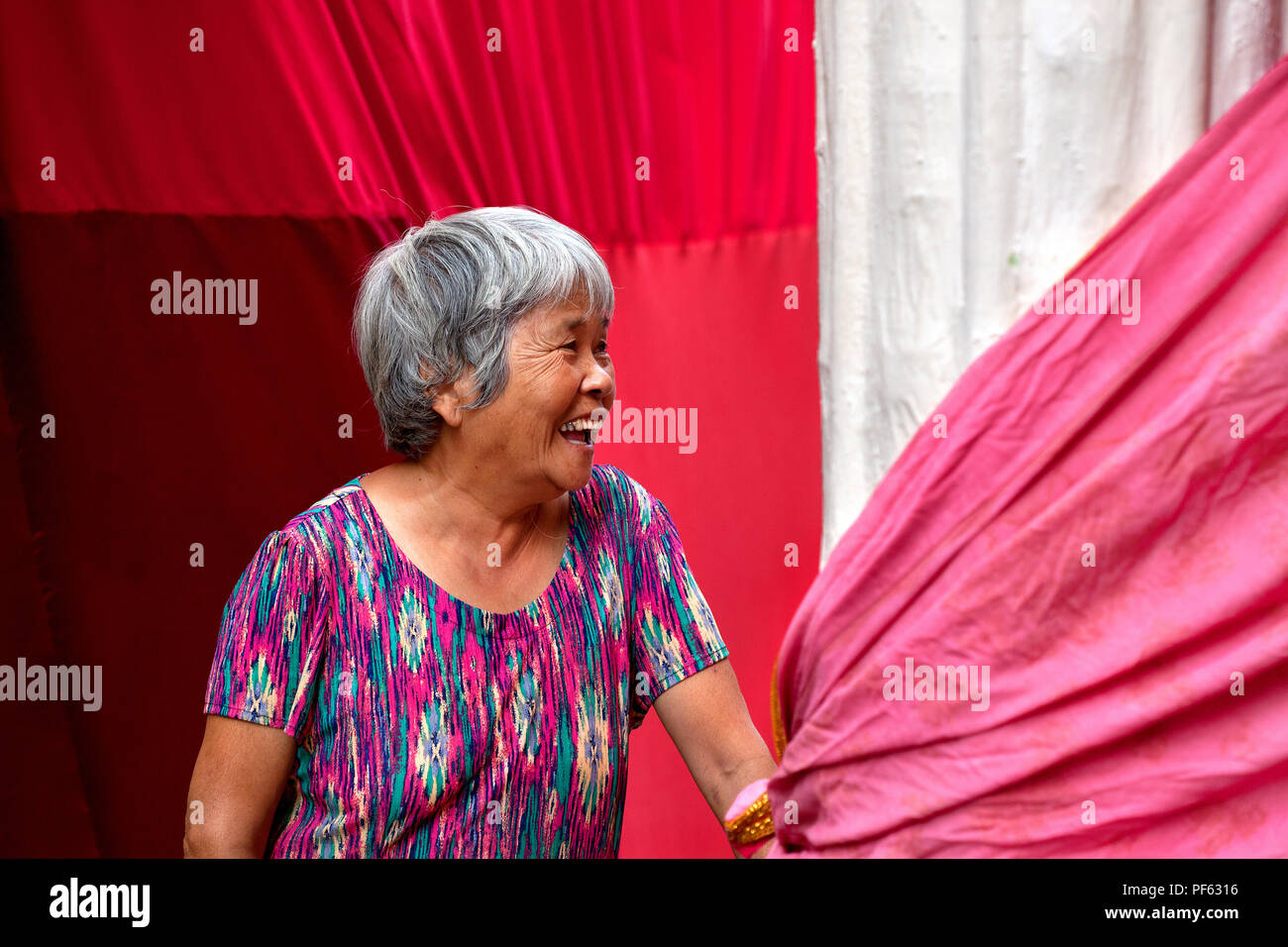 Older Chinese woman smiling for photo, Gracia, Barcelona. - Stock Image