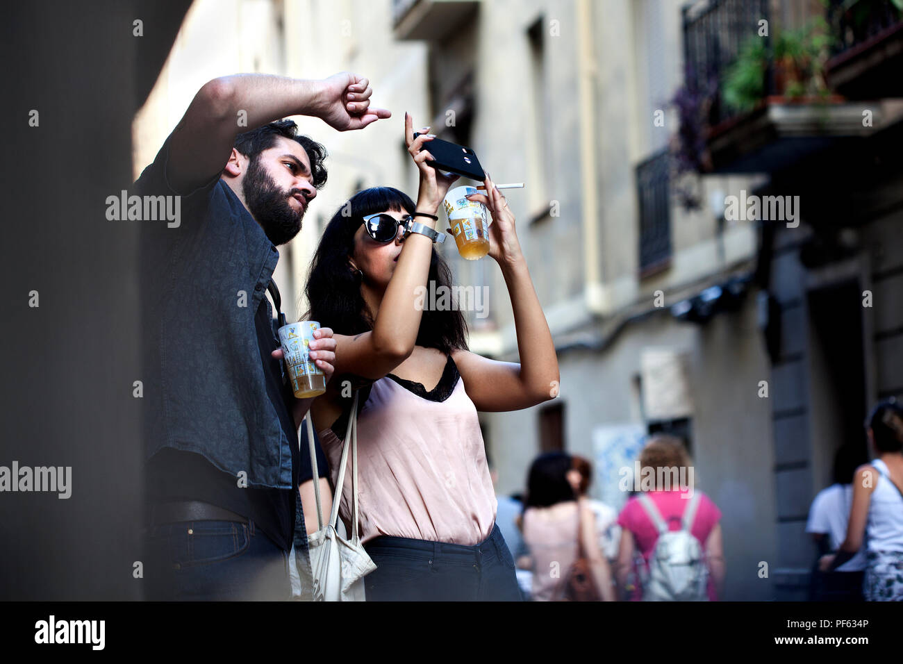 Trendy young couple taking photos on a smartphone, Barcelona, Spain. - Stock Image
