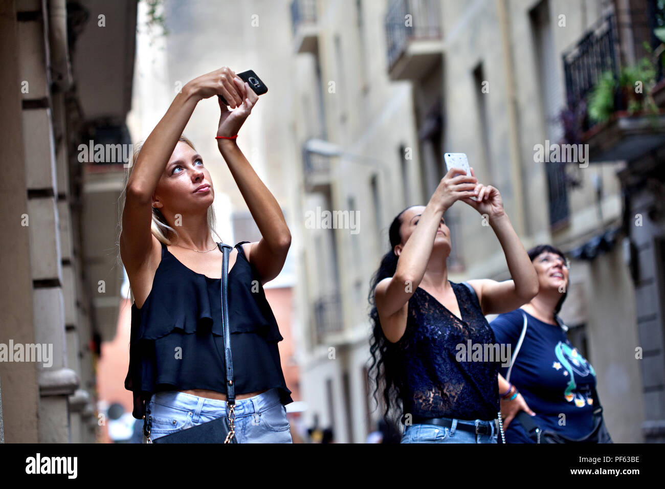 Young women taking photos on their smartphones, Gracia, Barcelona. - Stock Image
