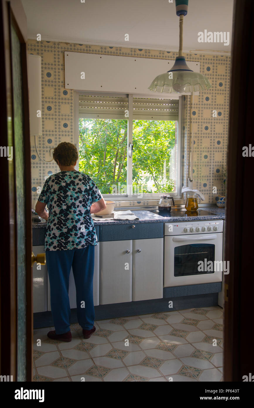 Mature woman working in the kitchen. - Stock Image