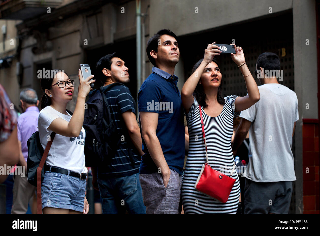 Tourists taking photos on their smartphones. Barcelona, Spain. - Stock Image