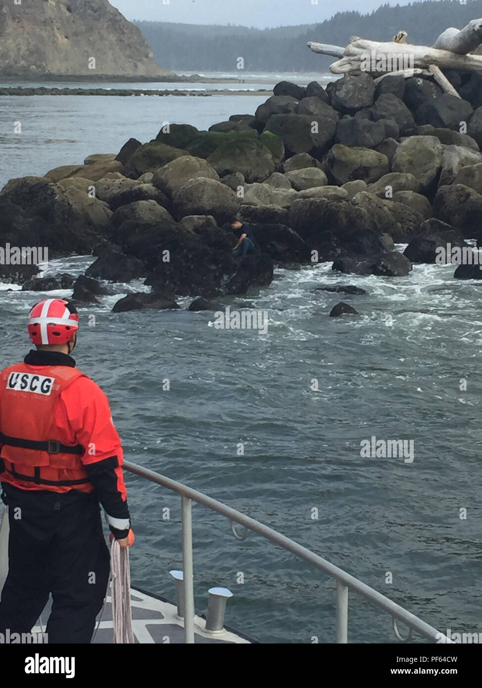 An injured swimmer sits on rocks as a Coast Guard boat crew aboard a 47-foot Motor Life Boat approaches his location to rescue him near La Push, Wash., Aug. 16, 2018.    The swimmer suffered lacerations on his arms and received medical assistance.    U.S. Coast Guard photo by Petty Officer 1st Class Louis Keating. - Stock Image