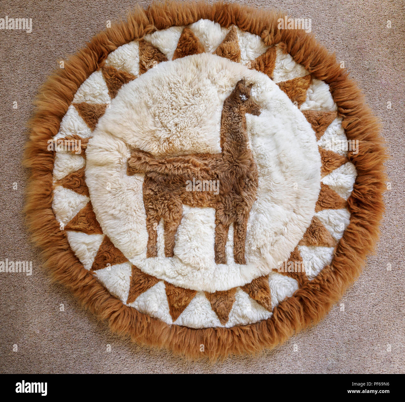 Typical Peruvian or Bolivian souvenir: a soft, fluffy patchwork rug hand crafted from pieces of alpaca skin to form a picture of an alpaca or llama - Stock Image