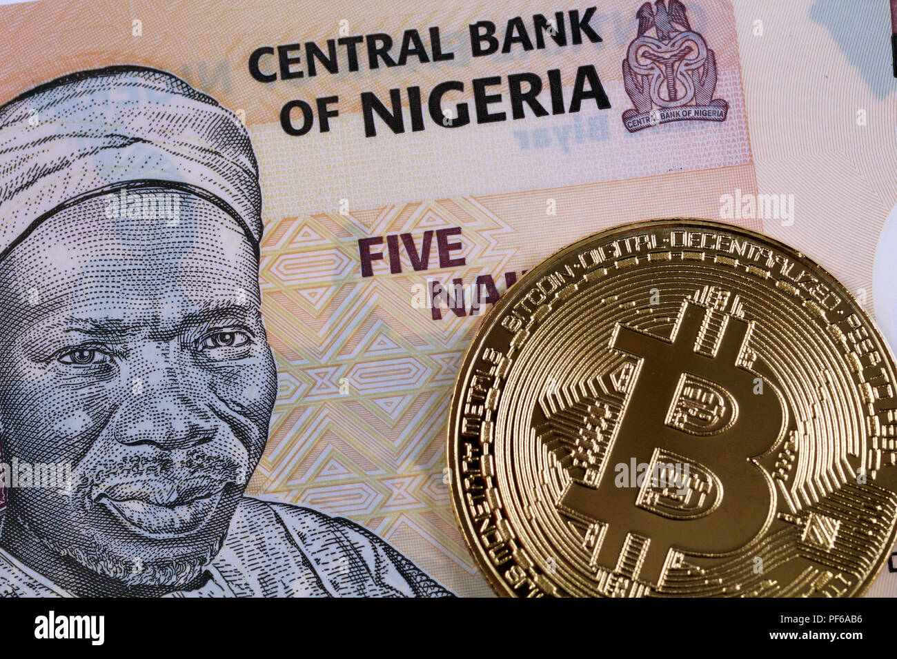 A close up image of a Nigerian five Naira bank note with a golden bitcoin - Stock Image