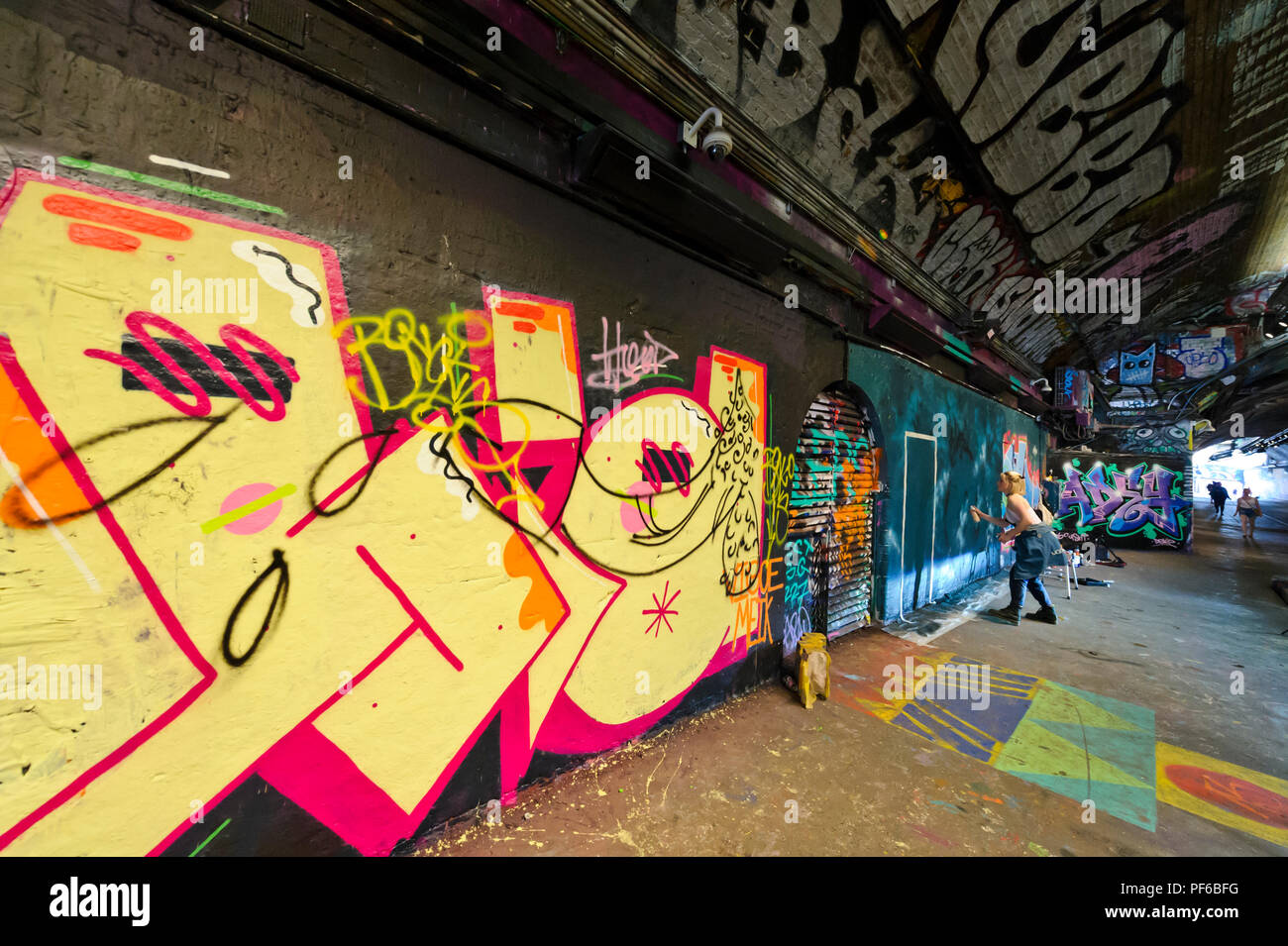 An artist spraying paint on the wall in a tunnel in London, London ...