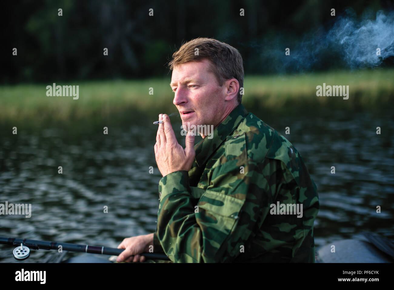 Fisherman smoking, camouflage clothing. - Stock Image