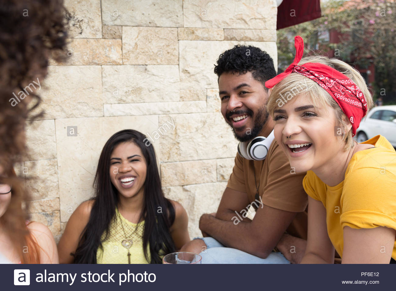 Multiracial group of students having a great time at cafe bar outdoor. Happy friends socializing in a party at restaurant outside. Summer, warm, frien - Stock Image
