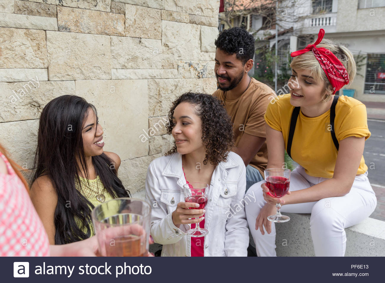 Mixed race people bonding and drinking at restaurant outside. Group of happy smiling students having a great time at cafe bar outdoor. Summer, warm, f - Stock Image
