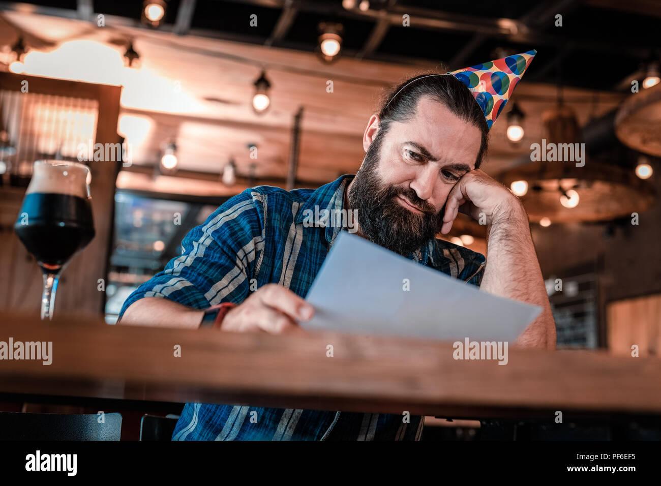 Dark-haired man overcoming midlife crisis sitting in bar - Stock Image