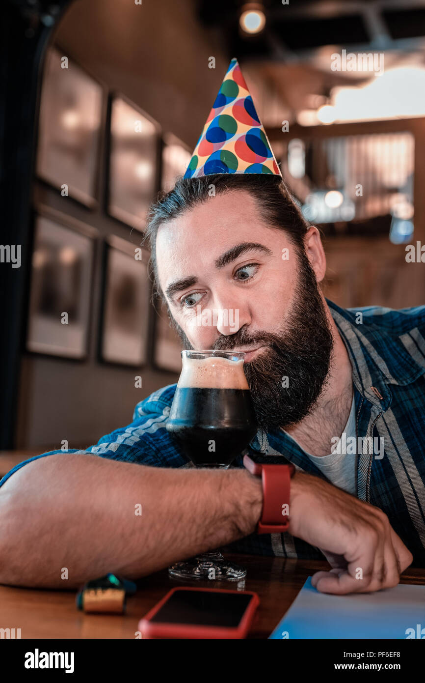 Funny bearded man sipping some dark beer celebrating birthday - Stock Image