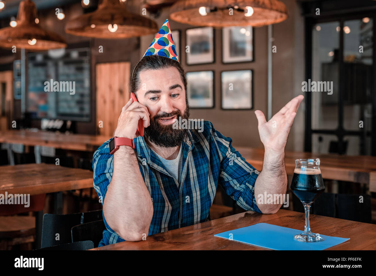 Birthday man feeling very emotional while speaking on the phone - Stock Image