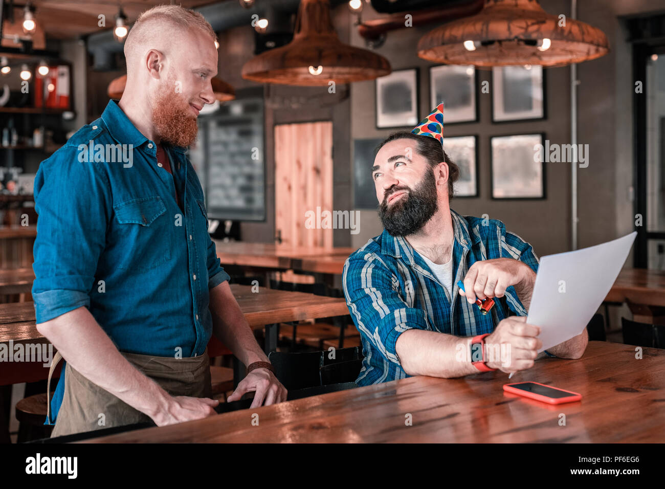 Satisfied man making his order speaking to the waiter in pub - Stock Image