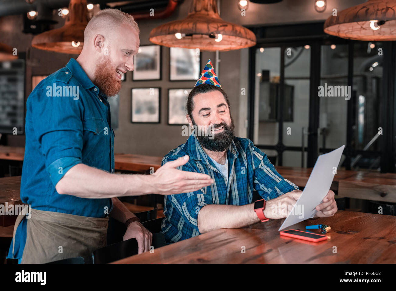 Bearded waiter recommending some good beer to his client - Stock Image