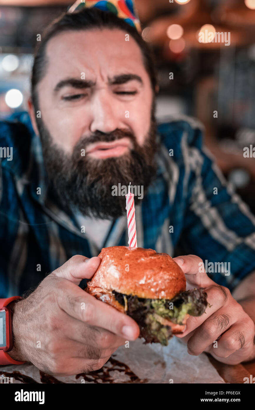 Emotional bearded man eating birthday burger in the pub - Stock Image