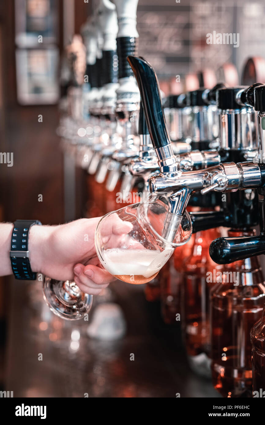 Barman pouring some dark craft beer into the glass - Stock Image