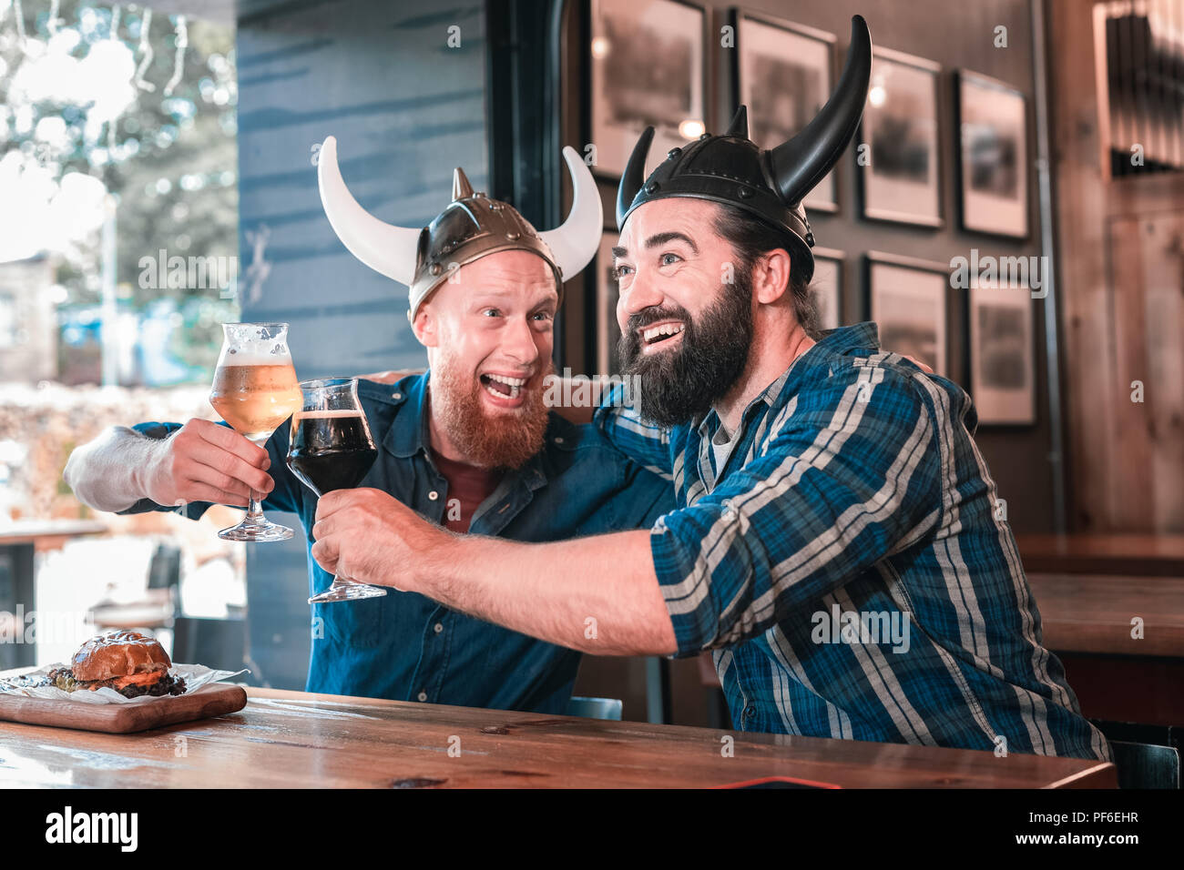 Two bearded men hugging celebrating victory winning of their football team - Stock Image